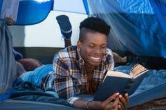 Equipe o livro de leitura ao encontrar-se na barraca fotos de stock royalty free