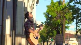 Equipe o músico da rua em uma camisa que joga a guitarra no por do sol video estoque