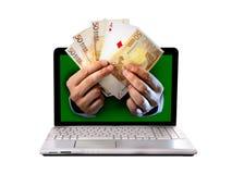 Equipe o outlaptop de vinda das mãos que guarda euro- cédulas e cartões de jogo do pôquer do ás Imagens de Stock