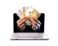 Equipe o outlaptop de vinda das mãos que guarda euro- cédulas e cartões de jogo do pôquer do ás Fotografia de Stock