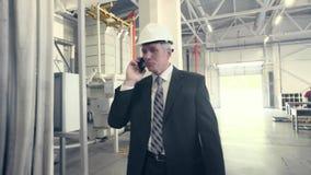 Equipe o passeio através da fábrica e a fala no telefone video estoque
