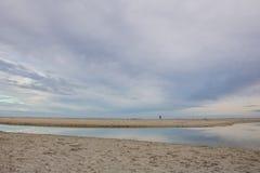 Equipe o passeio em uma praia com água que reflete as cores macias do céu na praia de Paarden Eiland no nascer do sol Fotos de Stock Royalty Free