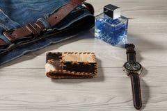 Equipe o perfume, o relógio, a bolsa e as calças de brim com correia de couro Imagens de Stock