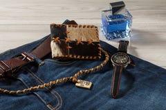 Equipe o perfume, o relógio e a bolsa em calças de brim com correia de couro Foto de Stock Royalty Free