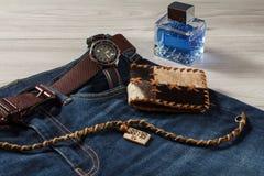 Equipe o perfume, o relógio e a bolsa na calças de ganga com correia de couro Foto de Stock