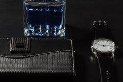 Equipe o perfume, relógio, caderno em um fundo preto Fotos de Stock