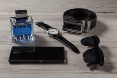 Equipe o perfume, relógio, correia de couro, telefone da venda, óculos de sol pretos Fotografia de Stock