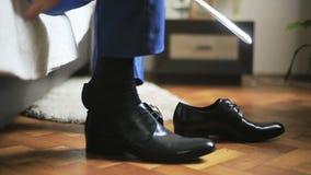 Equipe o pingamento de sapatas de couro pretas com uma ajuda da calçadeira que prepara-se para o evento formal video estoque