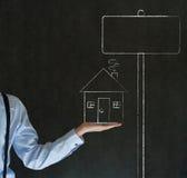 Homem com a casa da casa do giz ou os sig das vendas dos bens imobiliários imagens de stock