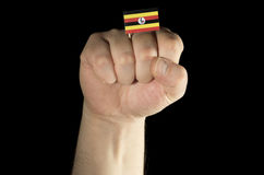 Equipe o punho da mão com a bandeira do Ugandan isolada no preto Fotografia de Stock Royalty Free