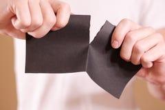 Equipe o rasgo de um pedaço de papel no folheto preto parcialmente vazio do inseto Fotografia de Stock