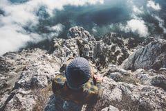 Equipe o relaxamento apenas no penhasco das montanhas rochosas sobre nuvens Imagens de Stock
