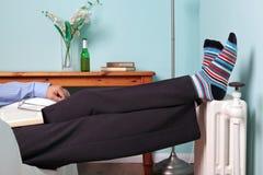 Equipe o relaxamento com seus pés acima no radiador Fotografia de Stock Royalty Free