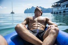 Equipe o relaxamento em uma jangada com câmera da ação Fotografia de Stock