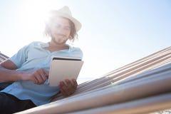 Equipe o relaxamento na rede e a utilização da tabuleta digital na praia Imagens de Stock Royalty Free