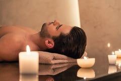 Equipe o relaxamento na tabela da massagem no centro asiático dos termas e do bem-estar imagem de stock