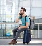 Equipe o relaxamento no aeroporto e a fala no telefone celular Fotos de Stock