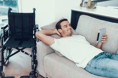 Equipe o relaxamento no sofá com a tabuleta perto da cadeira de rodas fotografia de stock royalty free