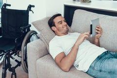 Equipe o relaxamento no sofá com a tabuleta perto da cadeira de rodas imagem de stock royalty free