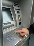 Equipe o ` s usando a máquina do ATM com cartões de dinheiro Close-up da mão que dá entrada ao código de PIN/pass no teclado da m imagens de stock royalty free