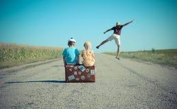 Equipe o salto e as duas crianças que sentam-se na mala de viagem Imagens de Stock