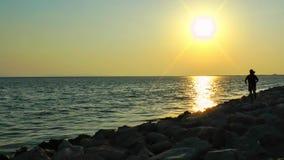 Equipe o salto nas rochas perto do beira-mar vídeos de arquivo