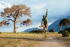 Equipe o salto no ar sobre a paisagem bonita do por do sol Fotografia de Stock Royalty Free