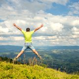 Equipe o salto no pico da montanha Imagem de Stock Royalty Free