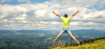 Equipe o salto no pico da montanha Imagem de Stock