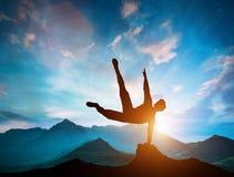 Equipe o salto sobre rochas na ação do parkour nas montanhas Imagem de Stock