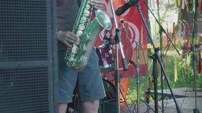 Equipe o saxofone dos jogos na fase durante o concerto busked video estoque