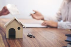 Equipe o sinal um seguro home em empréstimos hipotecarios, posse do agente do agente foto de stock