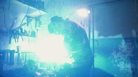 Equipe o soldador em trabalhos de máscara na garagem filme