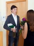 Equipe o sorriso e dê o grupo de flores a sua esposa Fotos de Stock Royalty Free