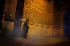 Equipe o suporte apenas na rua nevoenta sob o arco da rua da casa velha Fotos de Stock