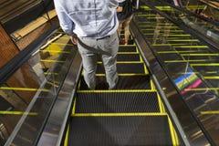 Equipe o suporte na escada rolante em baixo na alameda shoping Imagem de Stock
