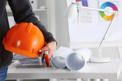 Equipe o terno vestindo do arquiteto que guarda o capacete, estando no escritório imagem de stock