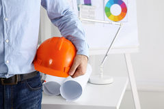 Equipe o terno vestindo do arquiteto que guarda o capacete, estando no escritório imagem de stock royalty free