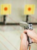 Equipe o tiro com a pistola pneumática no alvo praticando Imagens de Stock Royalty Free
