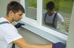 Equipe o trabalhador nas luvas protetoras que medem o tamanho externo do peitoril do metal do quadro e da janela do PVC foto de stock