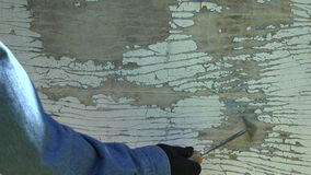 Equipe o trabalhador que limpa a pintura pealing branca velha com uma ferramenta, 4K filme