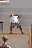 Equipe o trabalho em construir uma casa, fachada do cimento branco Foto de Stock