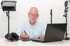 Equipe o trabalho em seus tabuleta e portátil de gráficos Imagens de Stock