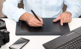 Equipe o trabalho em sua tabuleta de gráficos, fim acima das mãos Imagens de Stock Royalty Free