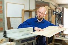 Equipe o trabalho em uma máquina na oficina de madeira Imagens de Stock Royalty Free