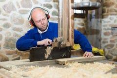 Equipe o trabalho em uma máquina na oficina de madeira Fotos de Stock