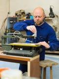 Equipe o trabalho em uma máquina na oficina de madeira Foto de Stock Royalty Free