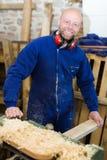 Equipe o trabalho em uma máquina na oficina de madeira Imagem de Stock