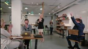 Equipe o trabalho no portátil descobre que as boas notícias que todos está feliz o felicitam e aplaudem equipe do negócio no escr video estoque