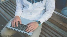 Equipe o trabalho no portátil, sentando-se no banco fora imagens de stock royalty free